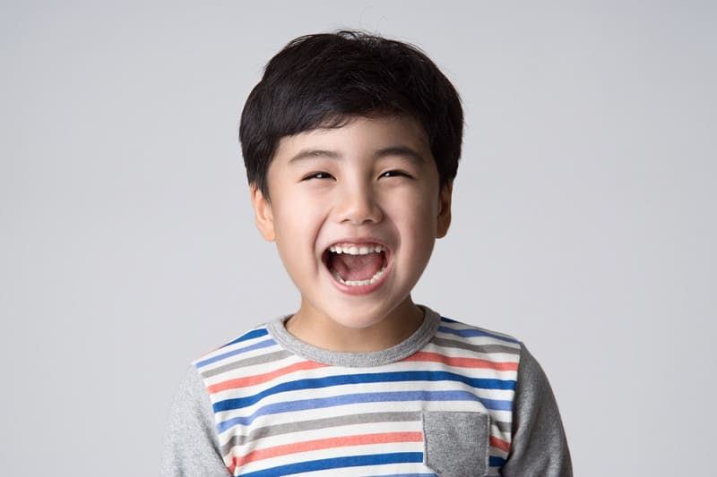 little boy with black hair wearing a striped shirt laughing