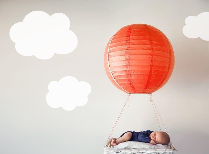 little boy sleeping in a blue onesie