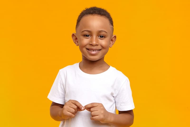 little boy smiling while posing in front of a yellow background