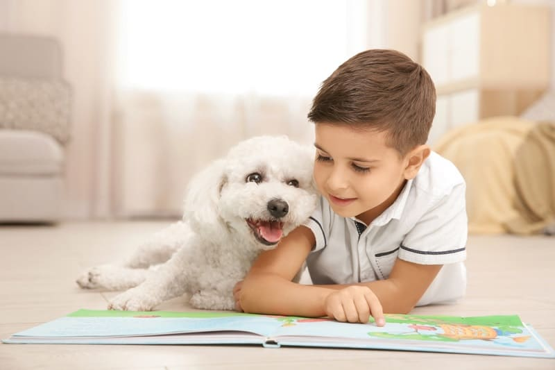 little boy reading on the floor with his cute puppy