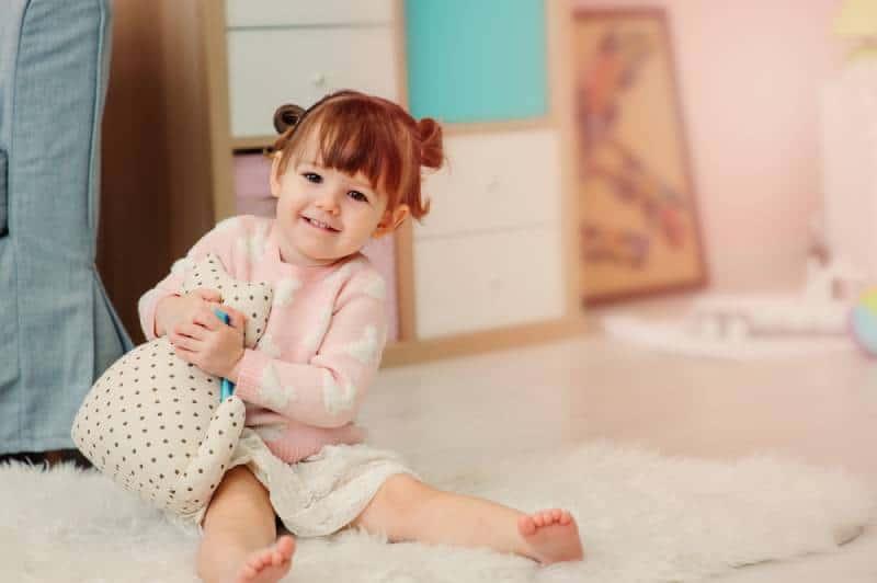little girl hugging her toy on the floor