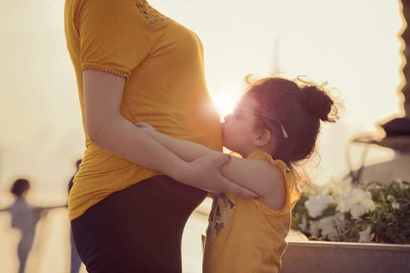 little girl kissing her pregnant mother's belly