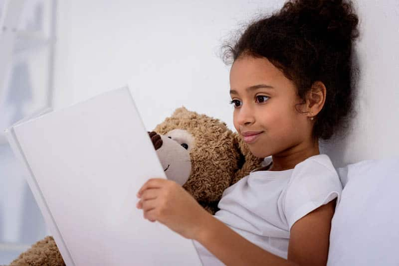 little girl reading a book and hugging teddy bear at home