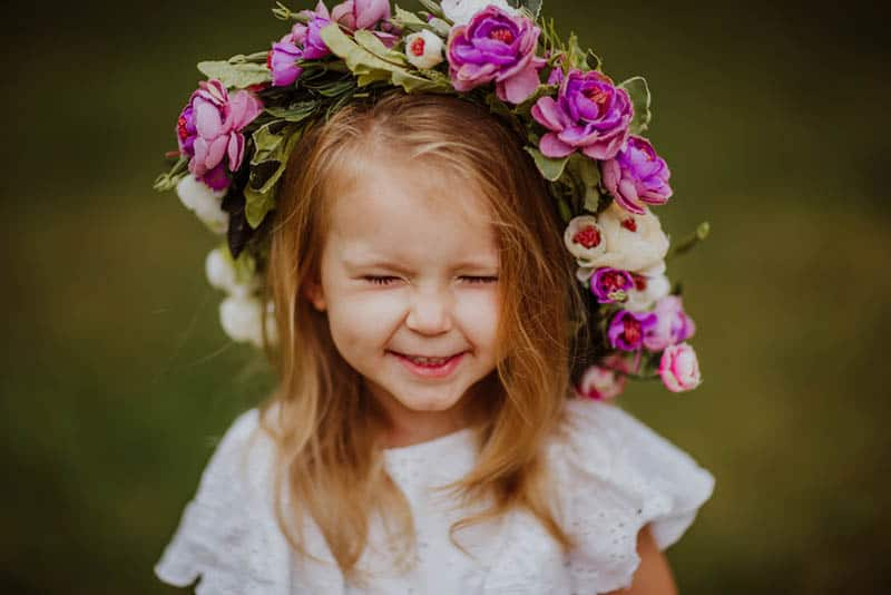 little girl smiling with flowers on the head