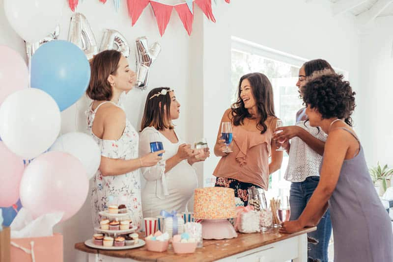 pregnant woman celebrating baby shower with friends at home