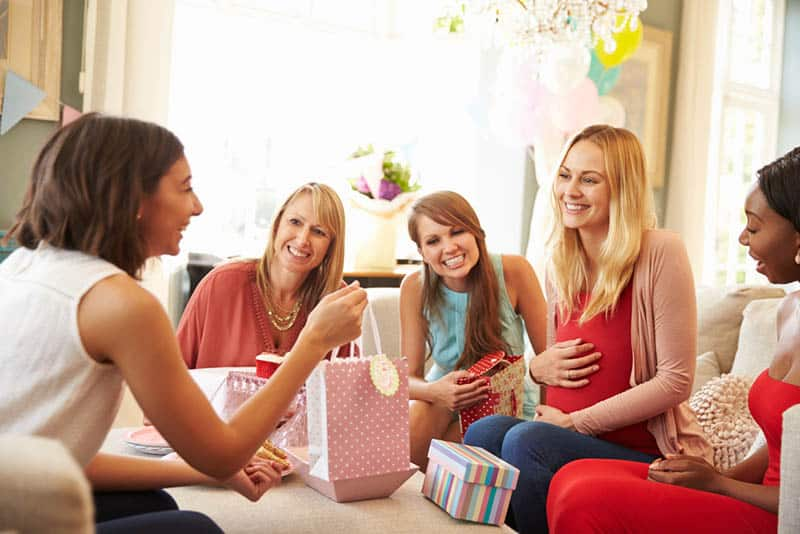pregnant woman with friends celebrating baby shower