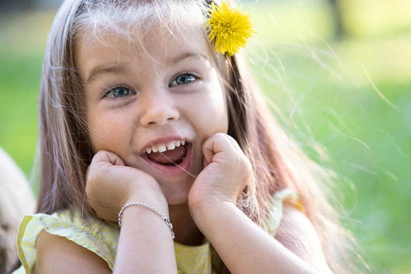 pretty girl with happy face expression smiling outdoors
