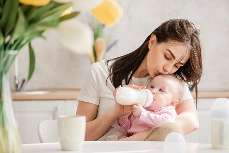 pretty woman kissing her baby in head and feeding with bottle of milk