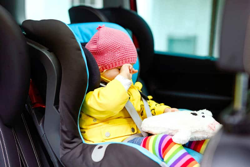 sleepy baby sitting in a car seat fasten with safety belt