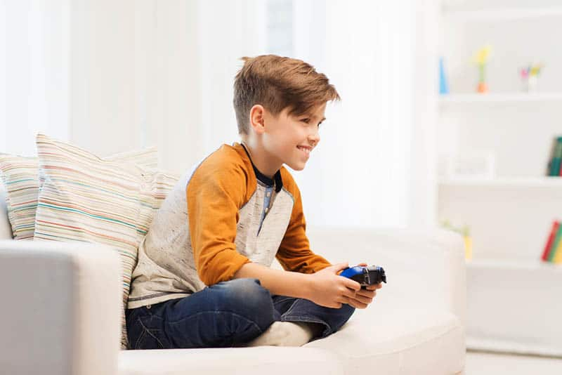 smiling little boy playing video games at home