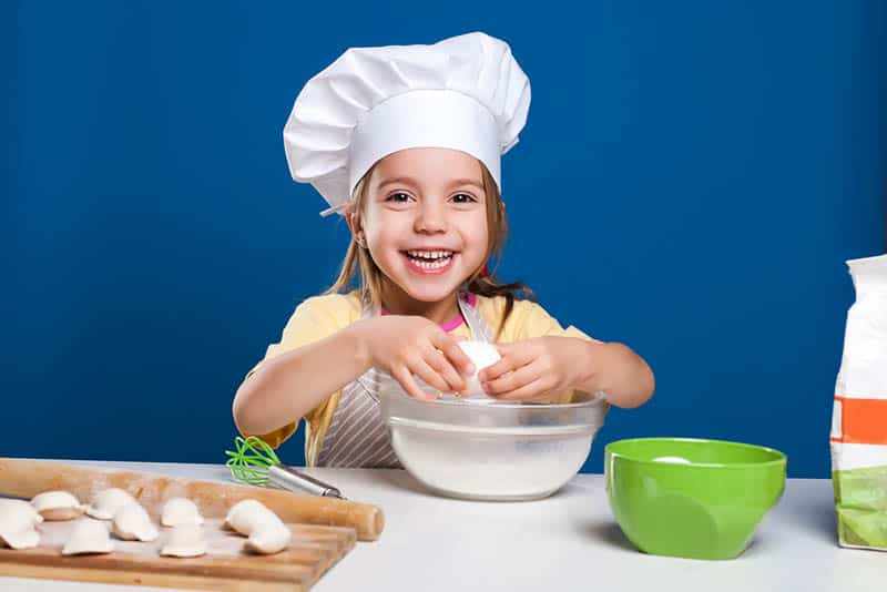 smiling little girl dressed up as a chef preparing a food