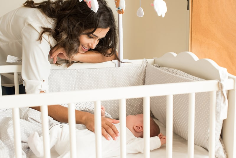 smiling young mother cuddling sleeping baby tummy in the crib