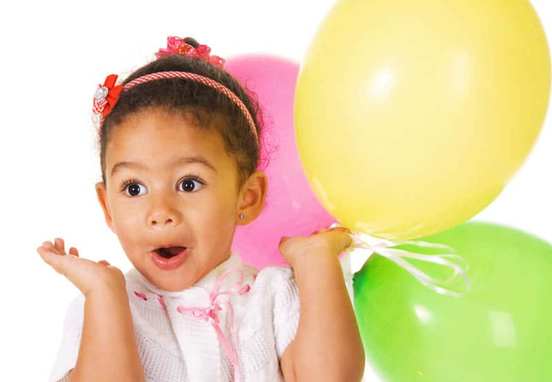 surprised little girl holding colorful balloons