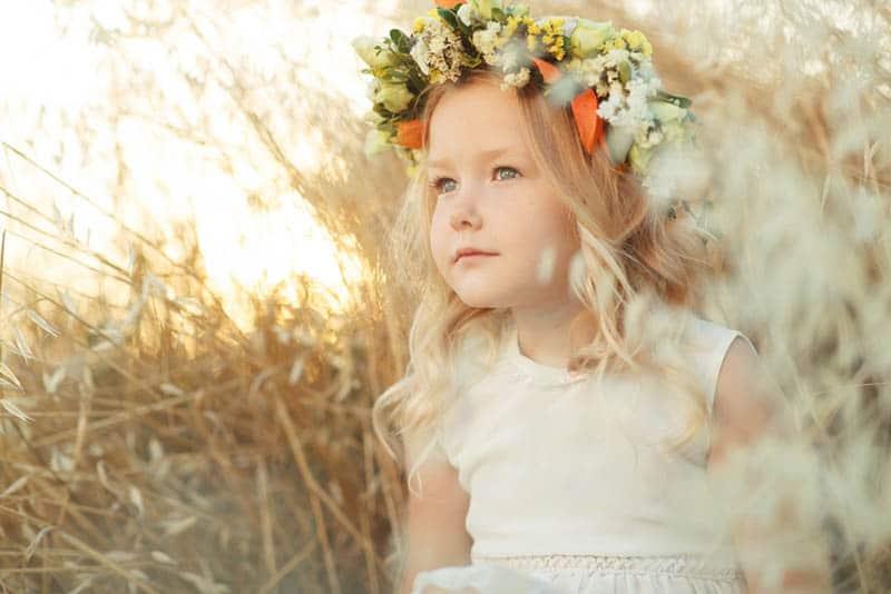 sweet little girl with flowers on her head sitting in meadow
