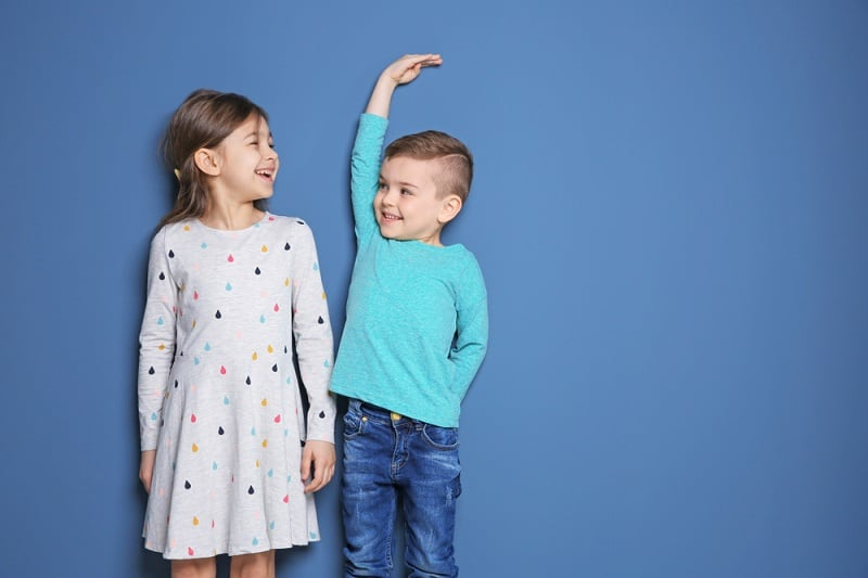 two siblings laughing while comparing their height