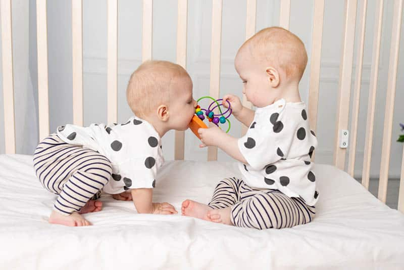 two twin babies playing in the crib