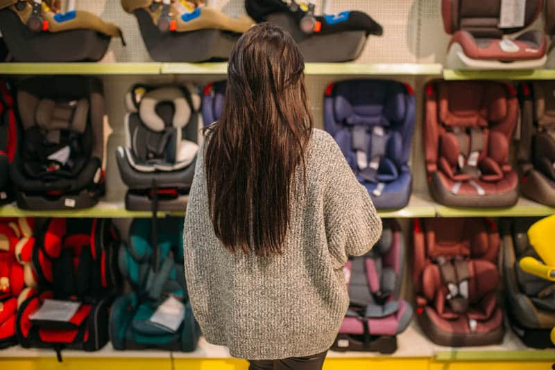 young woman standing against the baby car seats in store