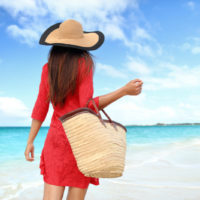 stylish woman walking by the ocean with a beach bag