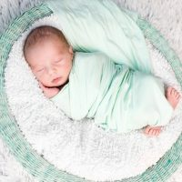 newborn baby sleeping while swaddled in a soft blanket