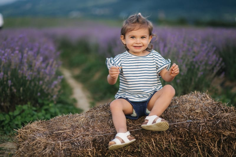 Adorable little girl sits on hay by the farm