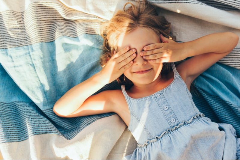 Beautiful blonde little girl lying on the blanket