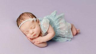 newborn baby sleeping on purple sheets