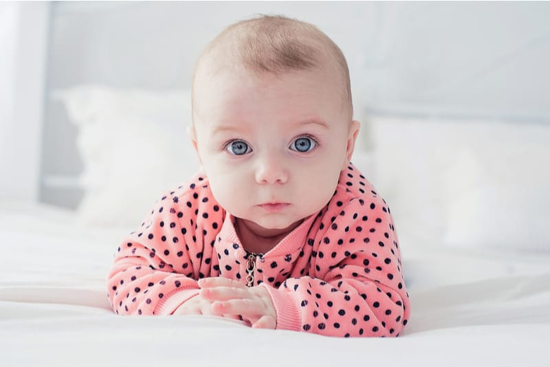 Cute baby lying on the white bed
