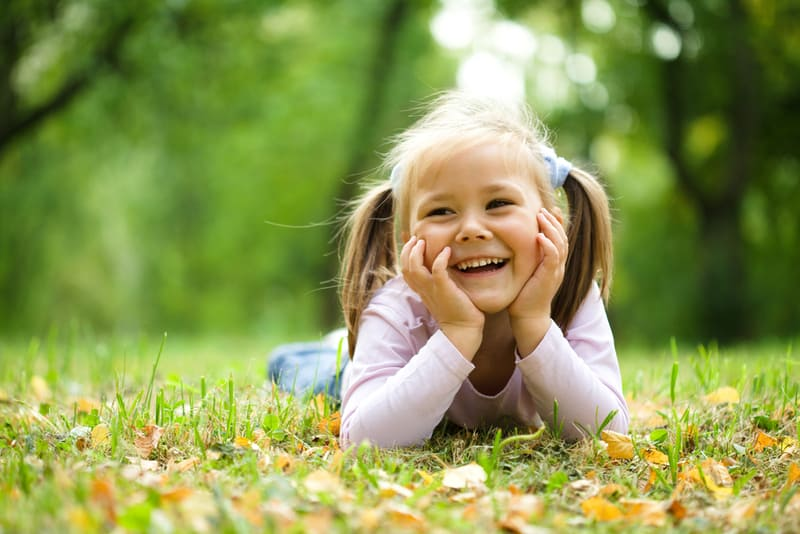 Cute little girl lying on the grass in park