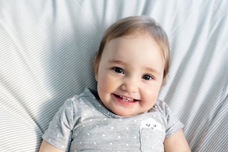 Cute smiling baby girl laying in the bed