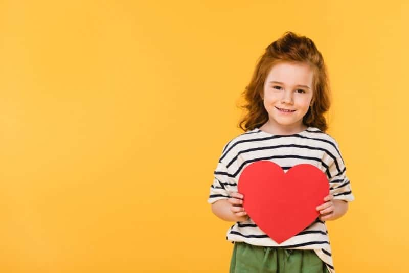 red-haired girl smiling and holding a red paper heart