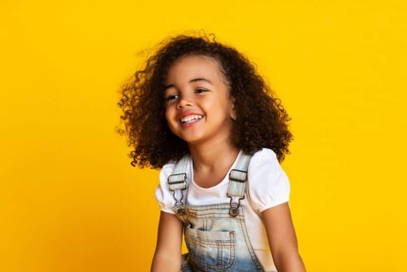 cute little girl with curly hair and a big smile