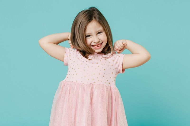 Little girl in a pink dress smiling
