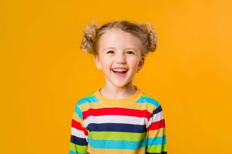 blonde little girl in a colorful shirt smiling