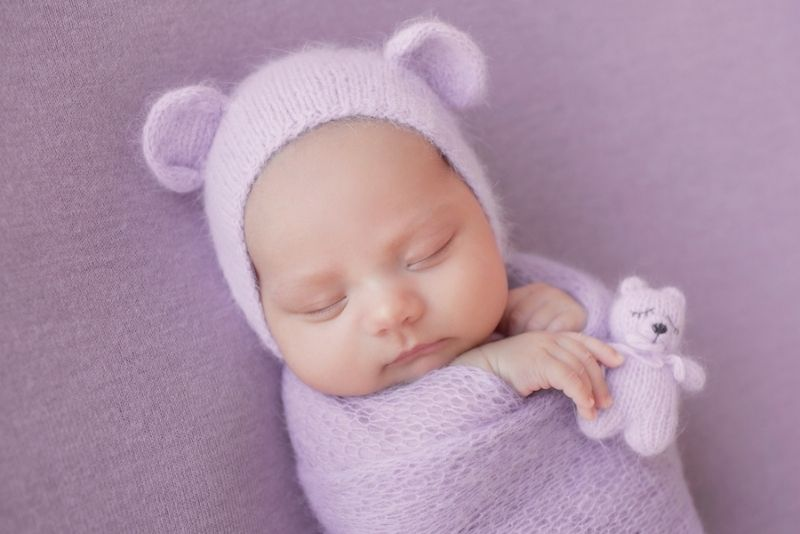 baby girl in a purple swaddle and funny hat with ears sleeping