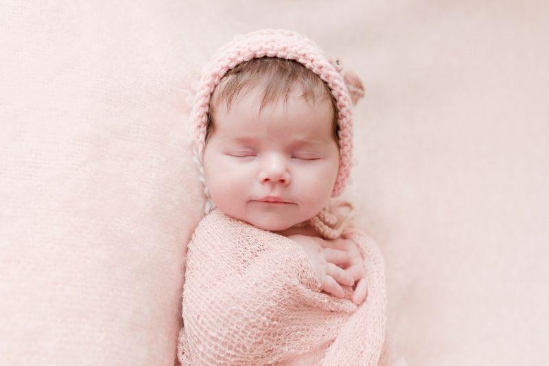 Newborn baby girl sleeping in pink swaddle