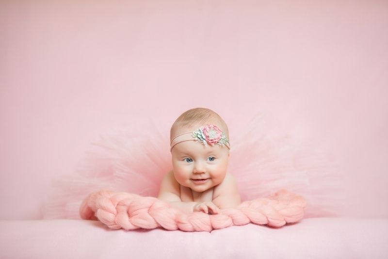 cute baby girl in a pink dress smiling