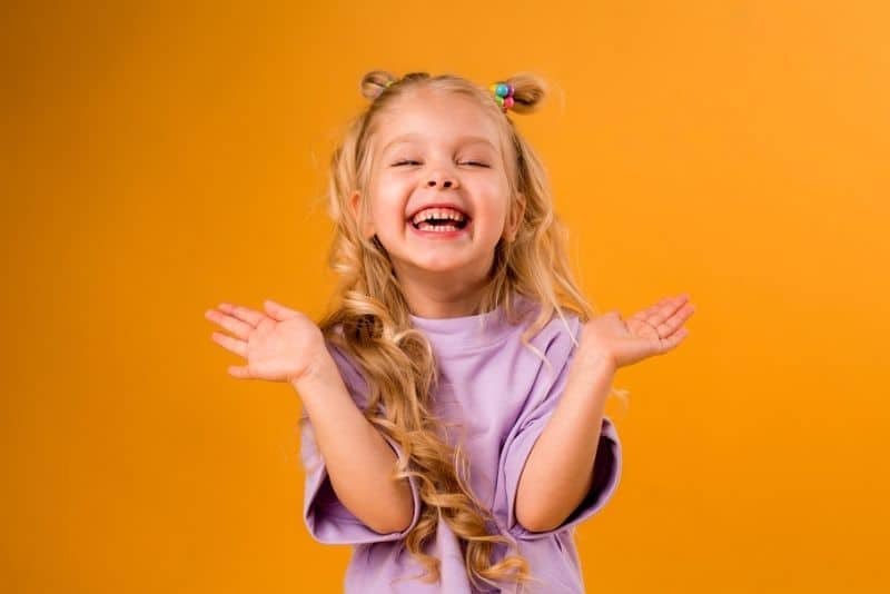 little blond girl in a purple t-shirt laughing