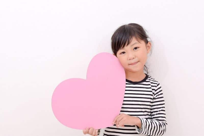 cute girl holding a pink paper heart and smiling