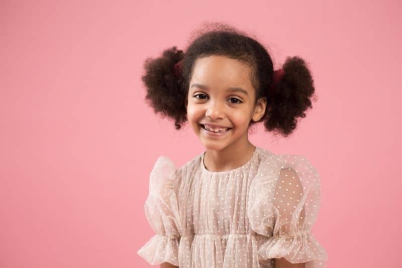 Cute girl in a beige dress smiling