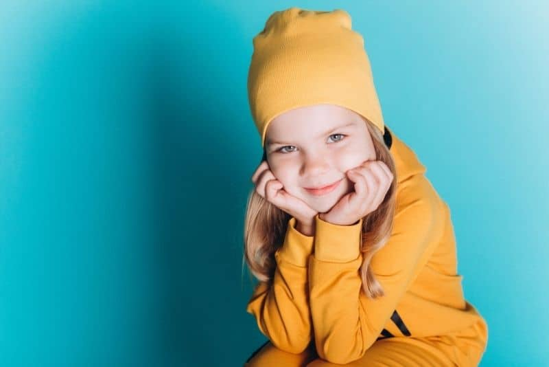 little blonde girl with a yellow hat smiling