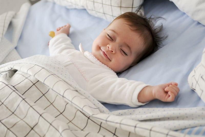 Smiling baby girl lying on a bed sleeping