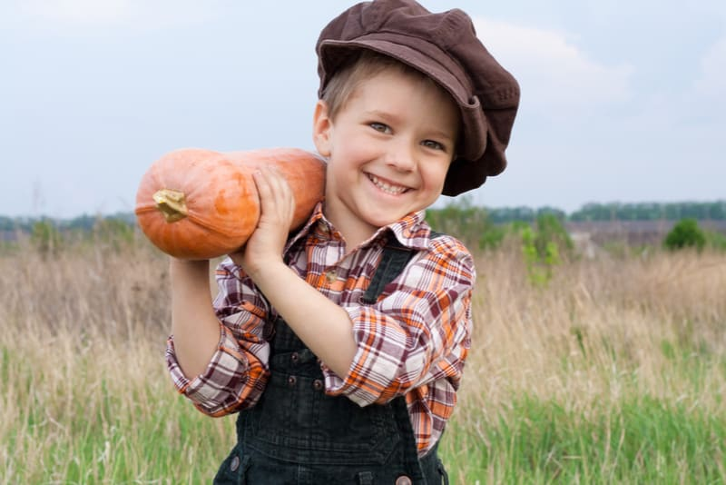 Smiling boy standing with pumpkin on his shoulder