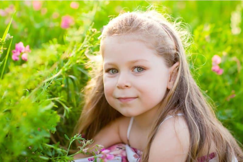 Sweet blonde little girl on the meadow