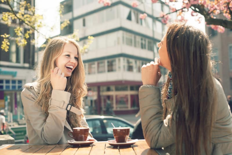 Two young women talk and drink coffee in cafe