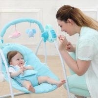 beautiful mother playing with her baby in a baby swing