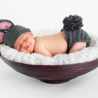 baby sleeping with his butt in the air in a small basket