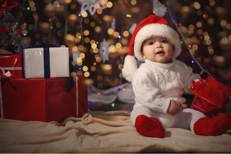 baby boy in a white knitted sweater and hat of Santa Claus