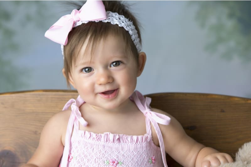 baby girl with bow in hair smiling