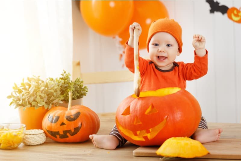 baby with a pumpkin for Halloween in the kitchen