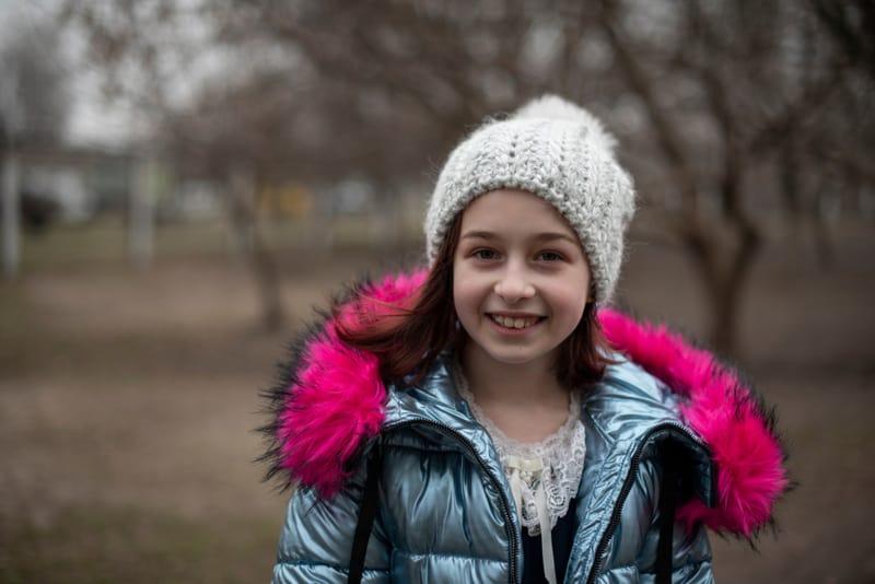 beautiful little girl wearing jacket in park